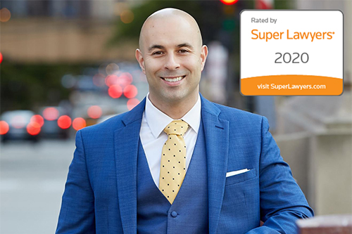 Chicago lawyer Matt Fakhoury standing on a sidewalk and leaning against a fence with the Super Lawyers 2020 rating logo